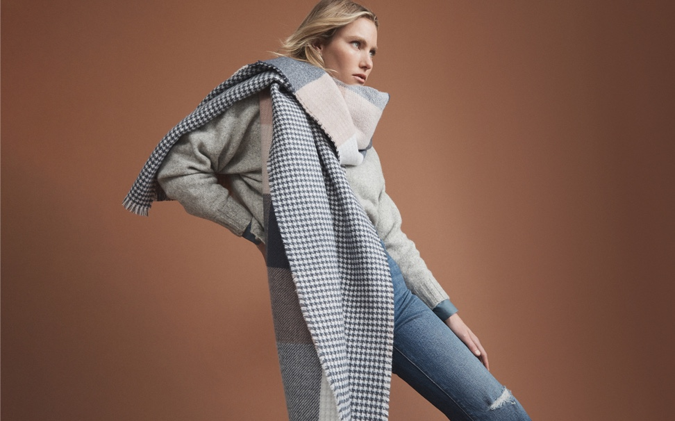 Model in women's knit, jeans and scarf